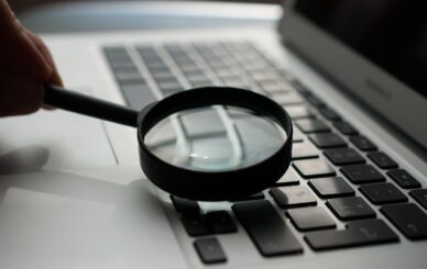 magnifying glass near gray laptop computer