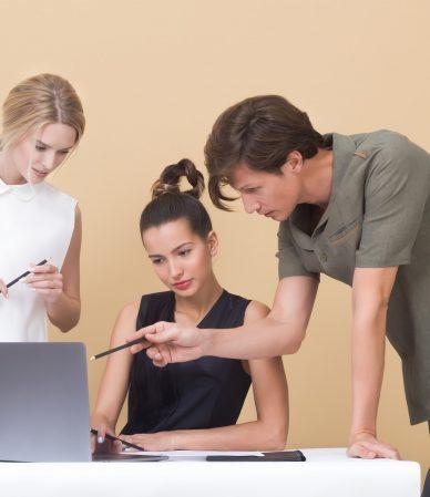 man teaching woman while pointing on gray laptop